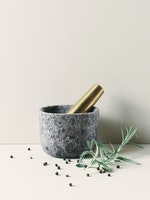 mortar in brown natural stone and pestle in brass.