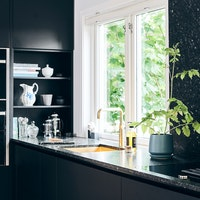Dark Scandinavian Kitchen style with black cabinetry and black natural stone kitchen worktop.