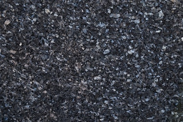 A deep blue stone surface with silver crystals