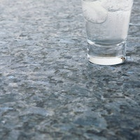 A grey stone surface with light blue crystals and a glass on top